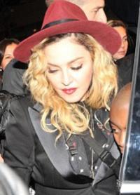 Певица вышла из машины в черном пиджаке и красной шляпе