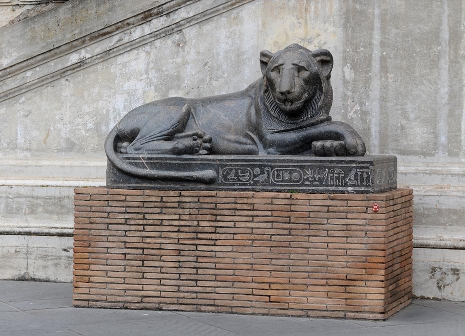 Фигура льва во дворе сосновой шишки